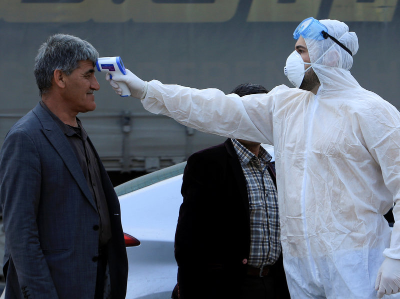 health worker checks a man's temperature at a checkpoint on the outskirts of Duhok, Iraq
